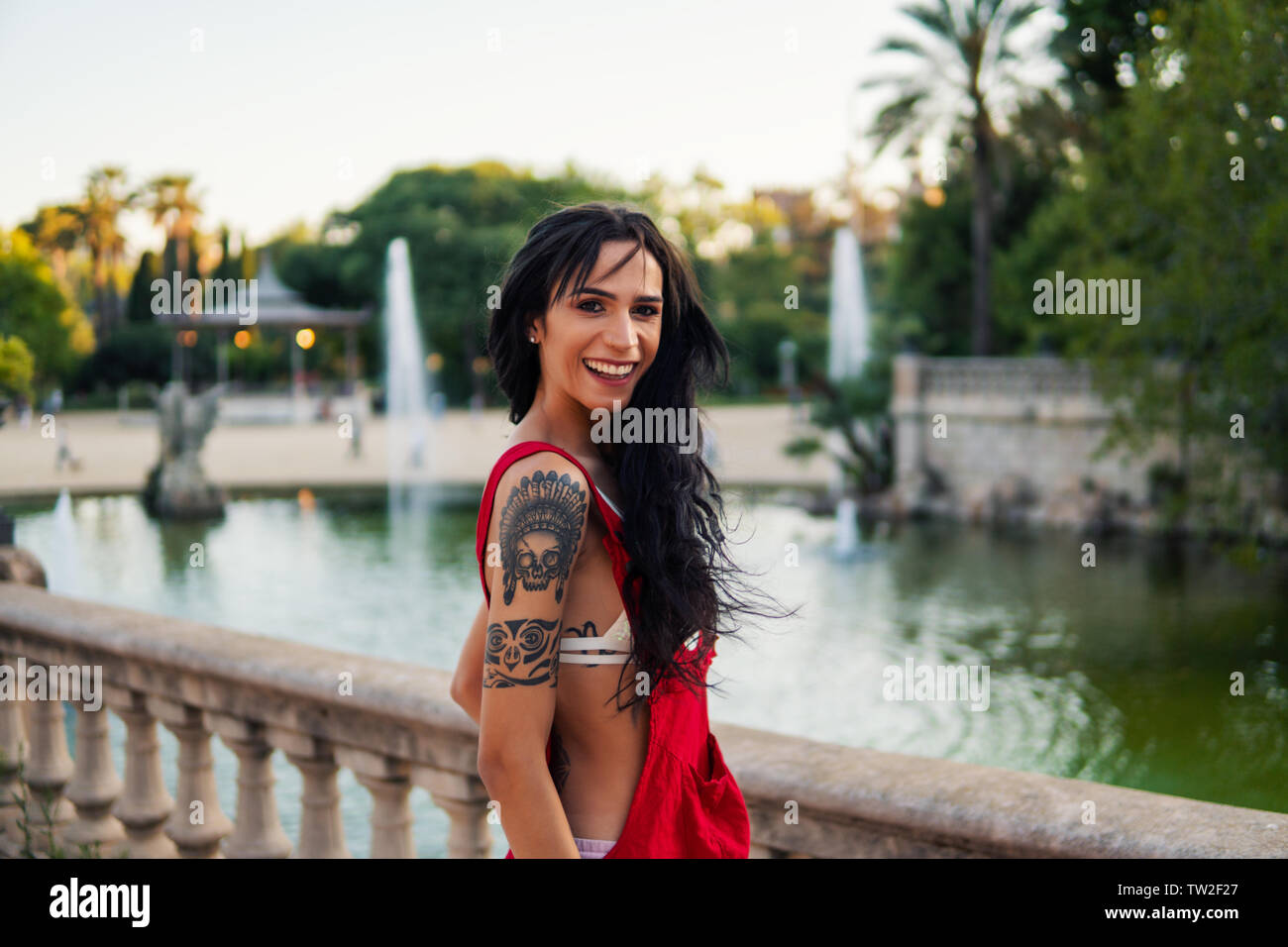 Ladyboy tattooed transgender model is dancing in the green park Stock Photo