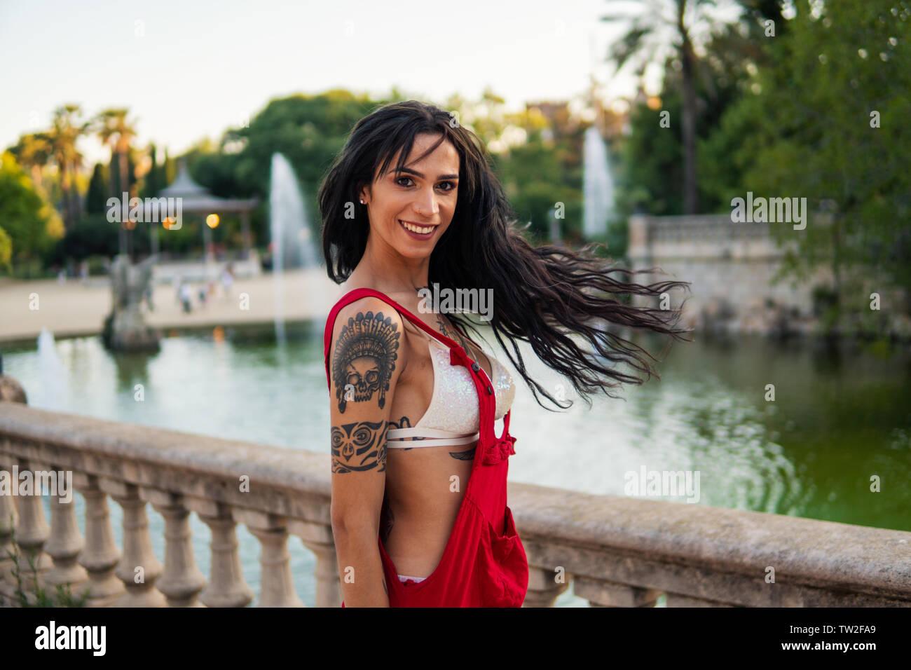 Ladyboy tattooed transgender model is dancing in the green park Stock Photo