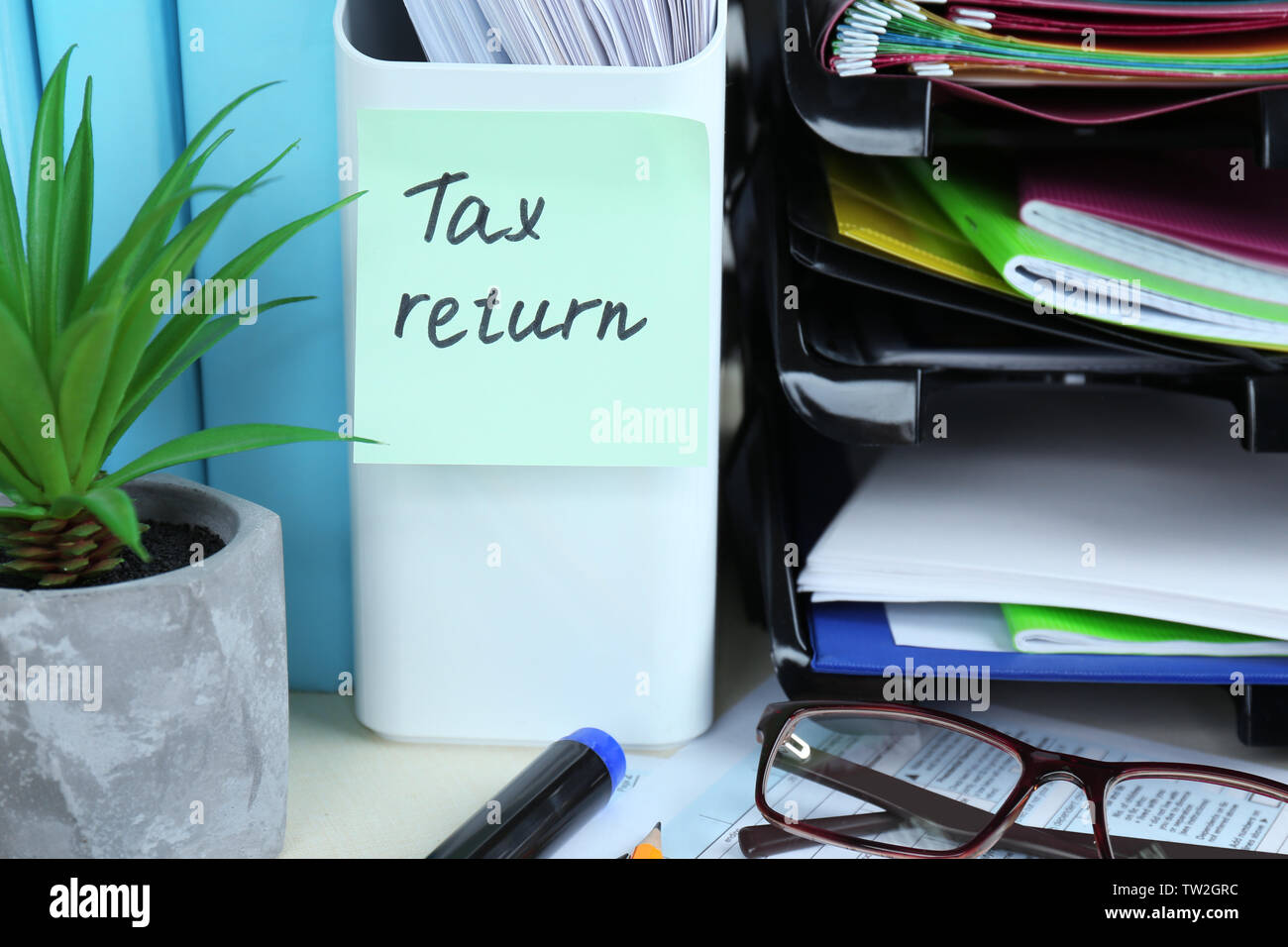 Note with TAX RETURN text and stationery on table - Stock Image