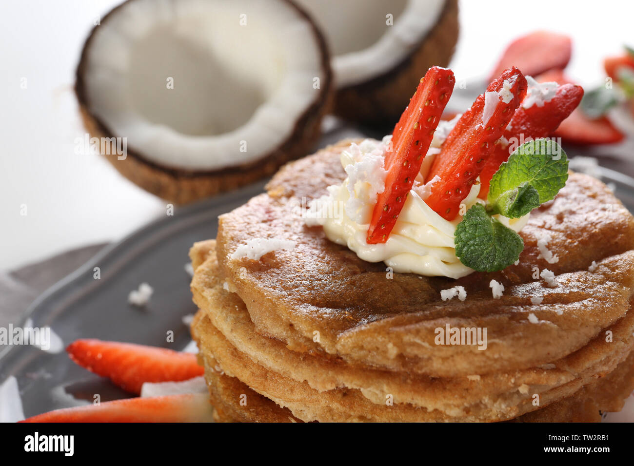 Stack of delicious coconut pancakes with strawberry and butter cream, close up Stock Photo