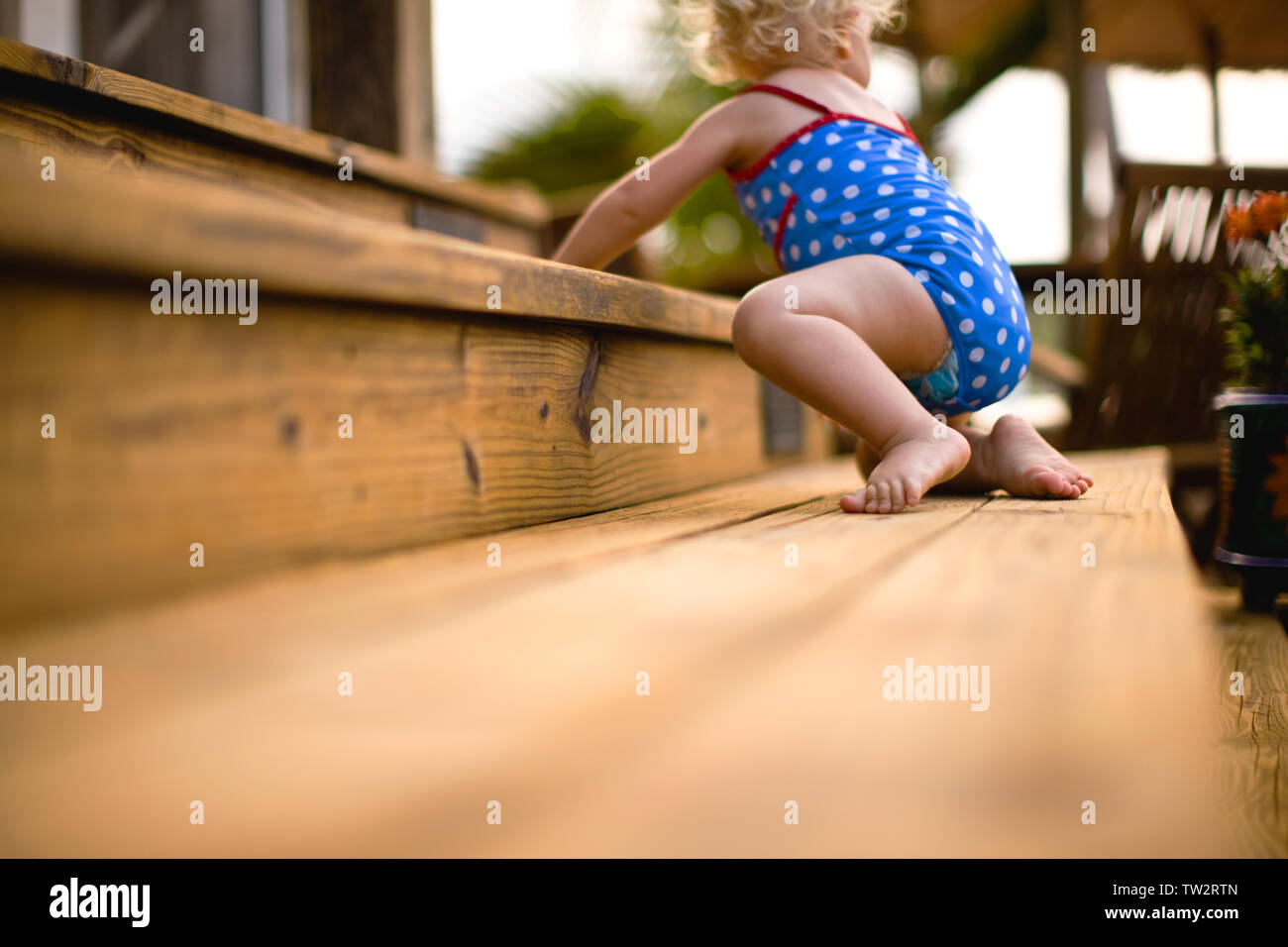 Baby crawling on wooden steps. - Stock Image