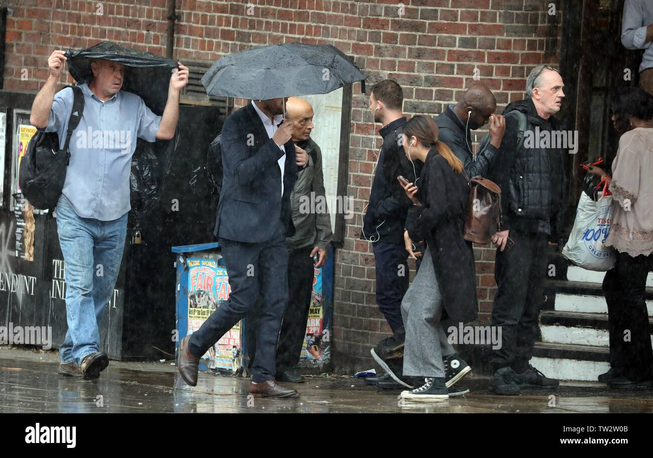 Wet Weather North London near East Finchley tube station today 18.6.19 caught commuters out on the way home with one of many heavy showers  sheltering - Stock Image
