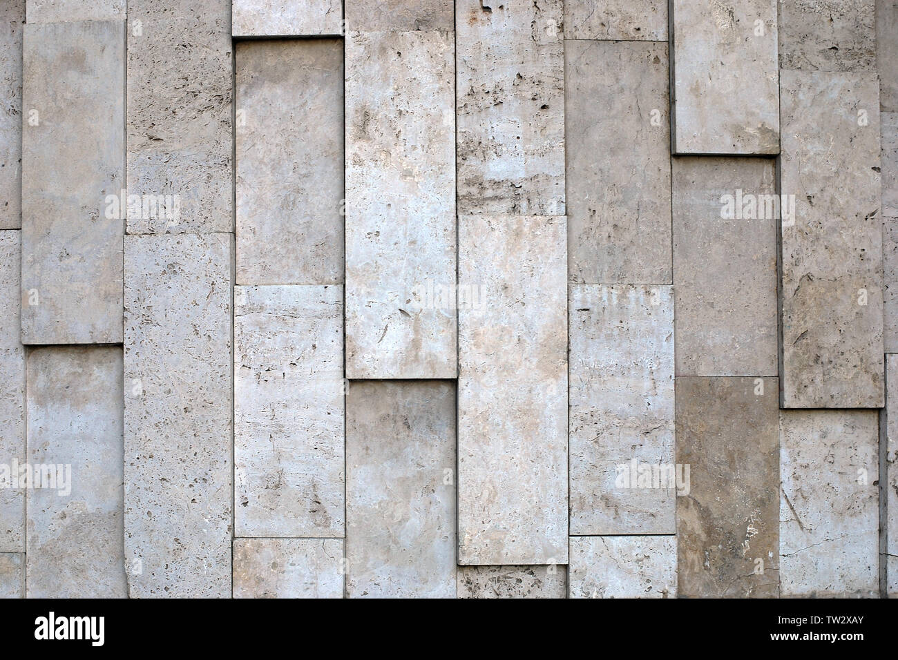 Natural stone wall of big vertical blocks of porous material in variety of beige tones. - Stock Image