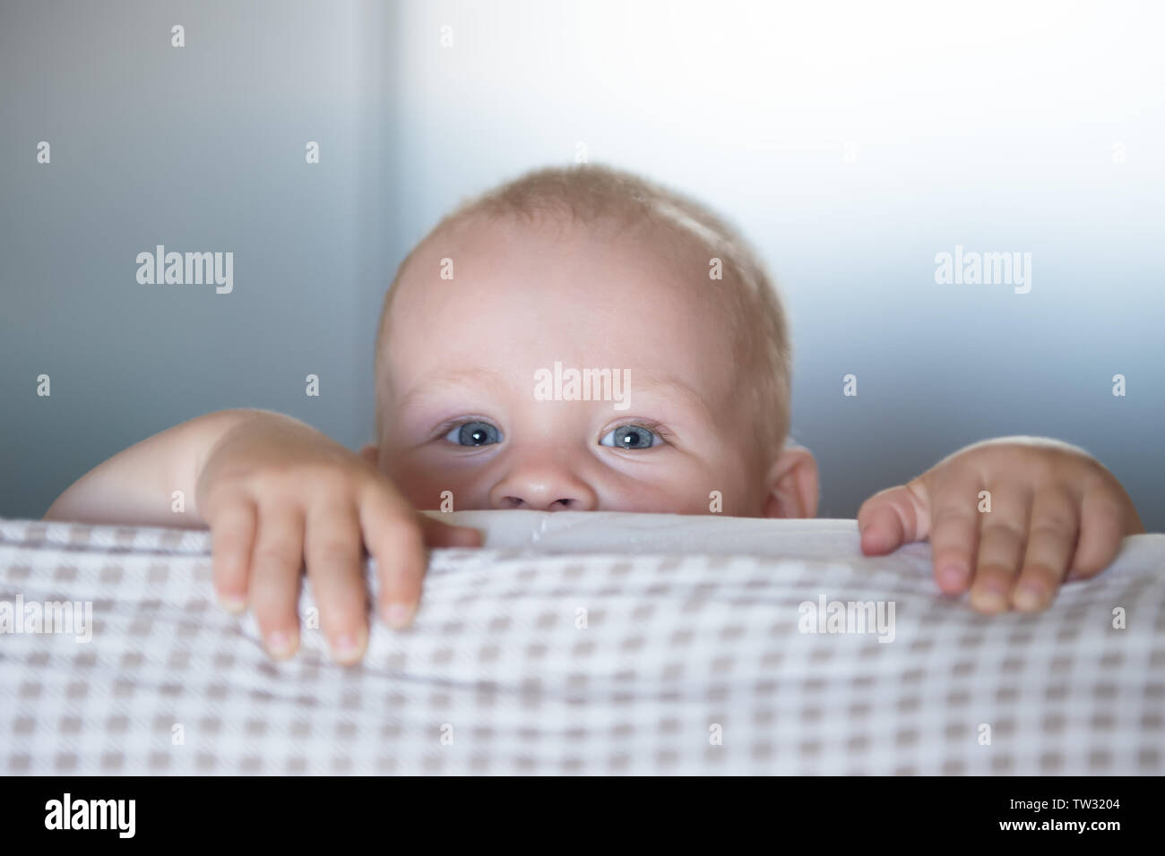 Little toddler boy playing on the bed. Cute kid smiling and hiding under cover. Palyful and mischievous eyes. Hide-and-seek. Children having fun playi Stock Photo