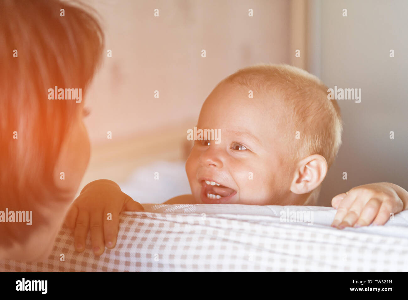 Little toddler boy playing on the bed. Cute kid smiling and hiding under cover. Palyful and mischievous eyes. Hide-and-seek. Children having fun playi - Stock Image
