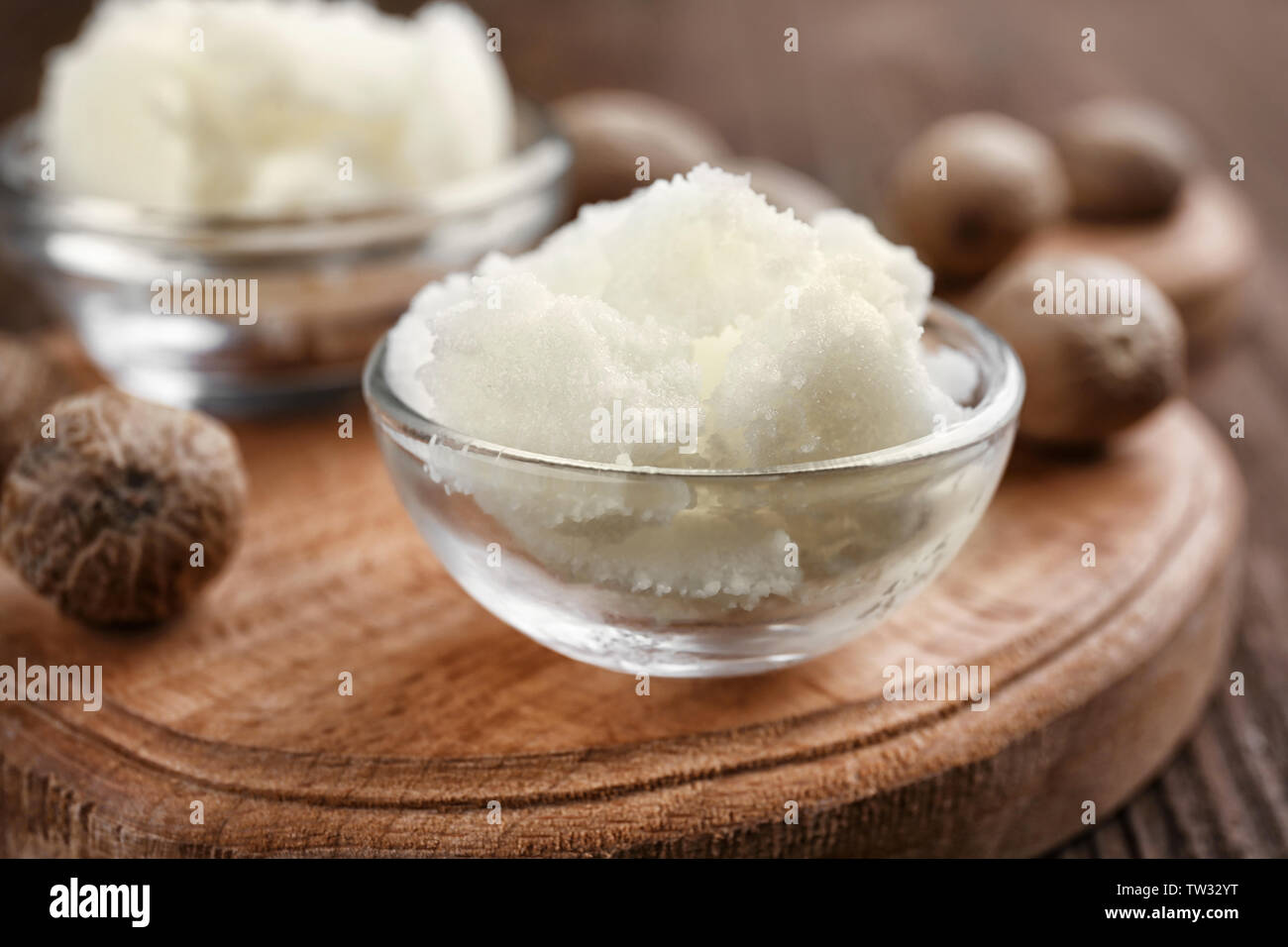 Shea butter in bowls on wooden background, close up Stock Photo