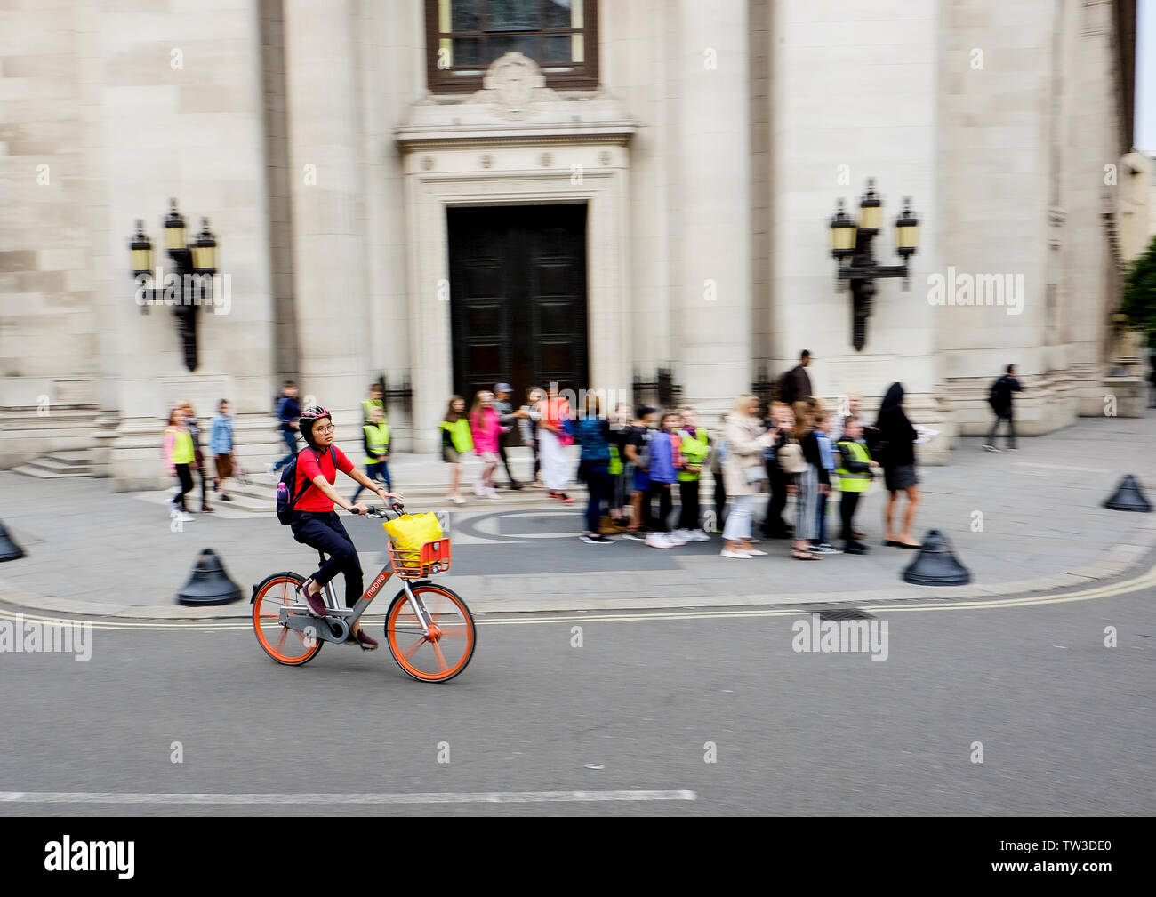 Motion blur capture of a female cyclist on a Mobike outside Freemasons Hall, Covent Garden, London - Stock Image