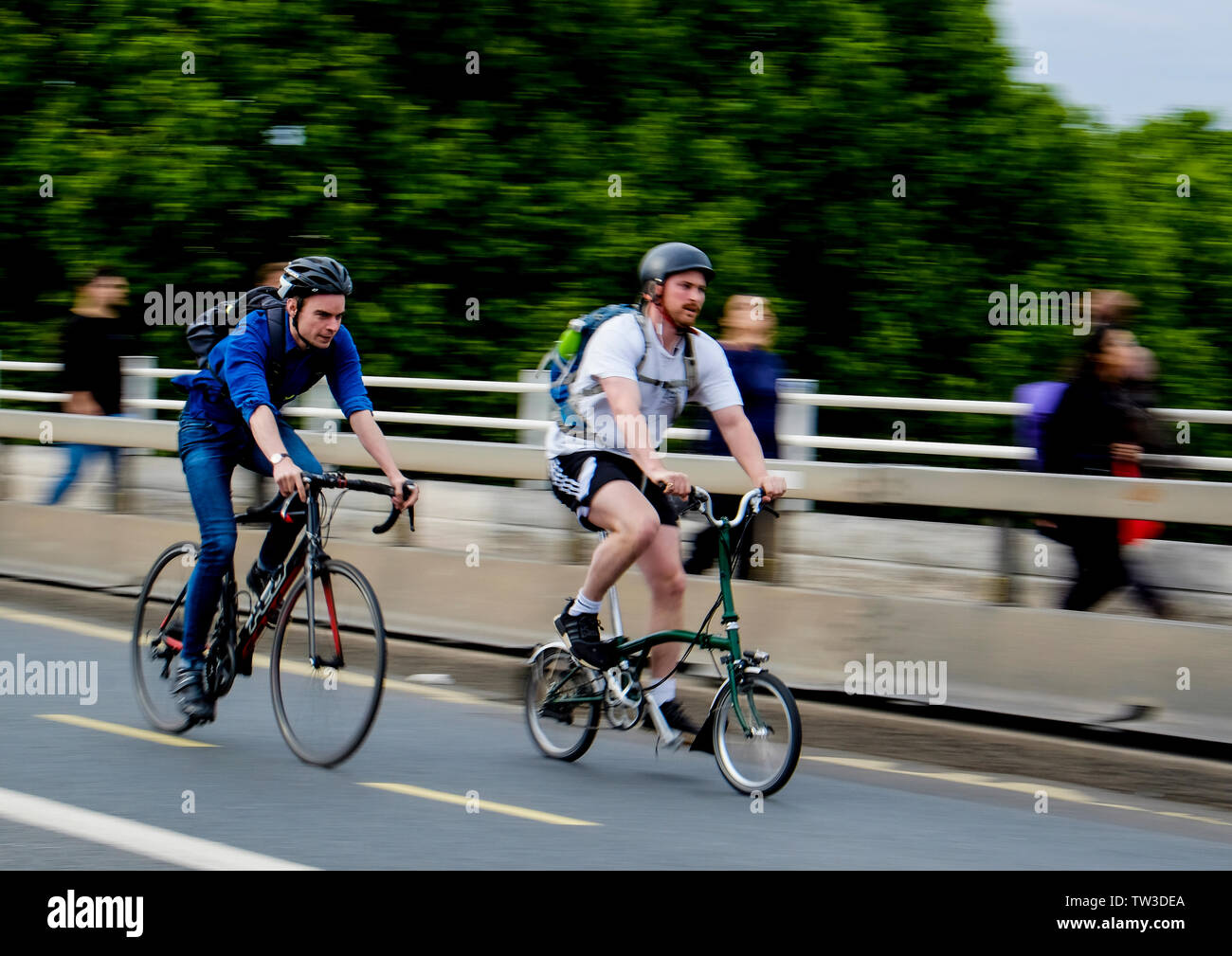 Motion blur capture of a male cyclist on a racing bike overtaking another on a folding bike on Waterloo Bridge, London - Stock Image