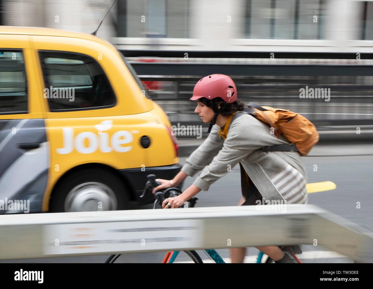 Motion blur capture of a female cyclist entering Waterloo Bridge, London - Stock Image