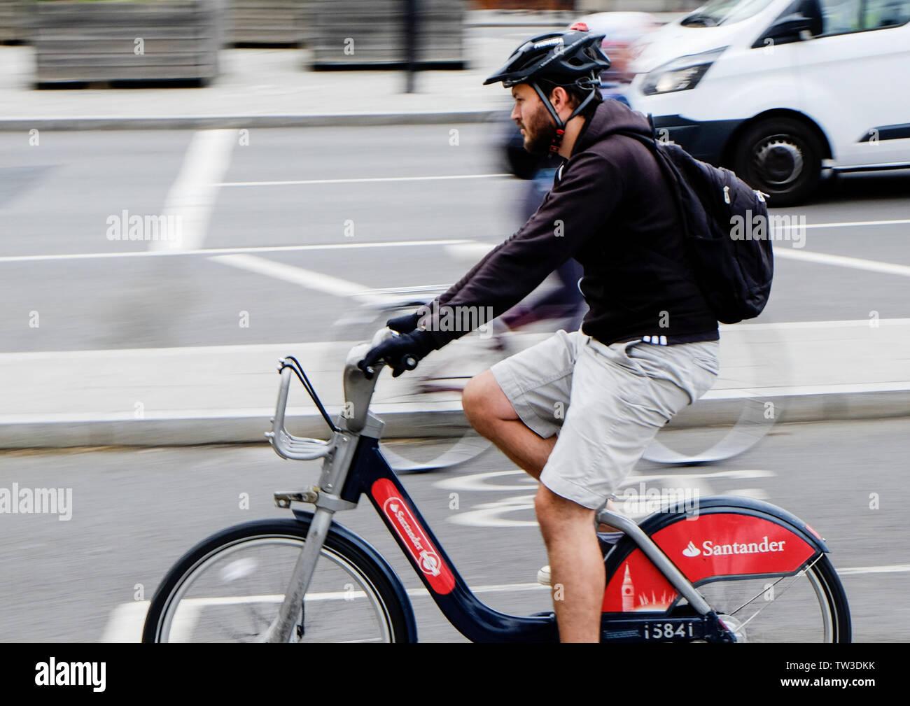 Motion blur capture of a male cyclist on a Santander bike in a cycle lane leaving Blackfriars Bridge, London - Stock Image
