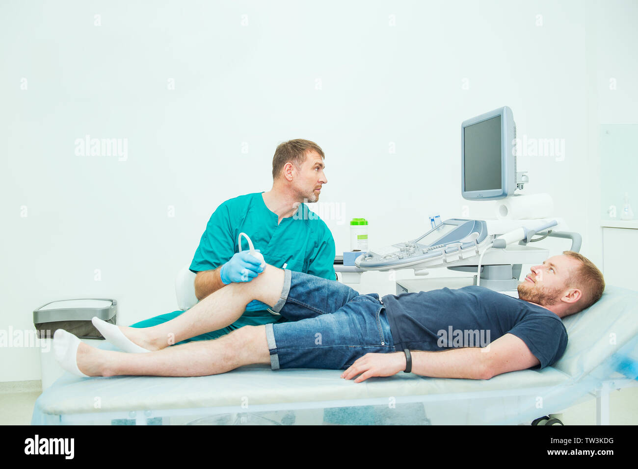 Orthopedist doctor conducting ultrasound examination of patient's knee in clinic. Ultrasound device scan. Sport Injury, Selective focus, copy space - Stock Image