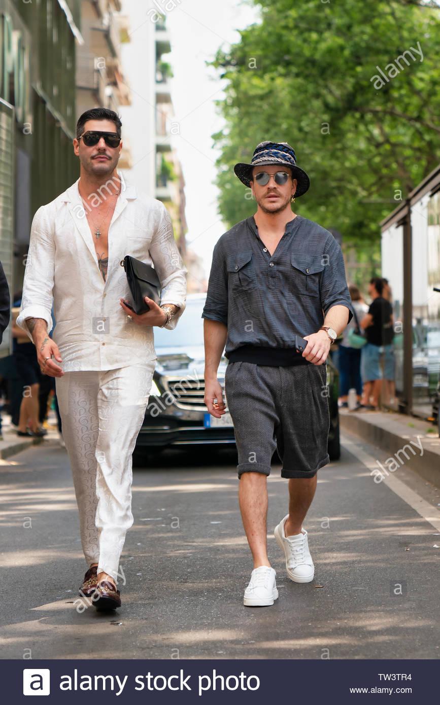 MILAN, ITALY - JUNE 15: Kadu Dantas is seen wearing white silk button shirt and pants and Peter Zawel wearing hat, grey button shirt and shorts outside Dolce & Gabbana during the Milan Men's Fashion Week Spring/Summer 2020 on June 15, 2019 in Milan, Italy. - Stock Image