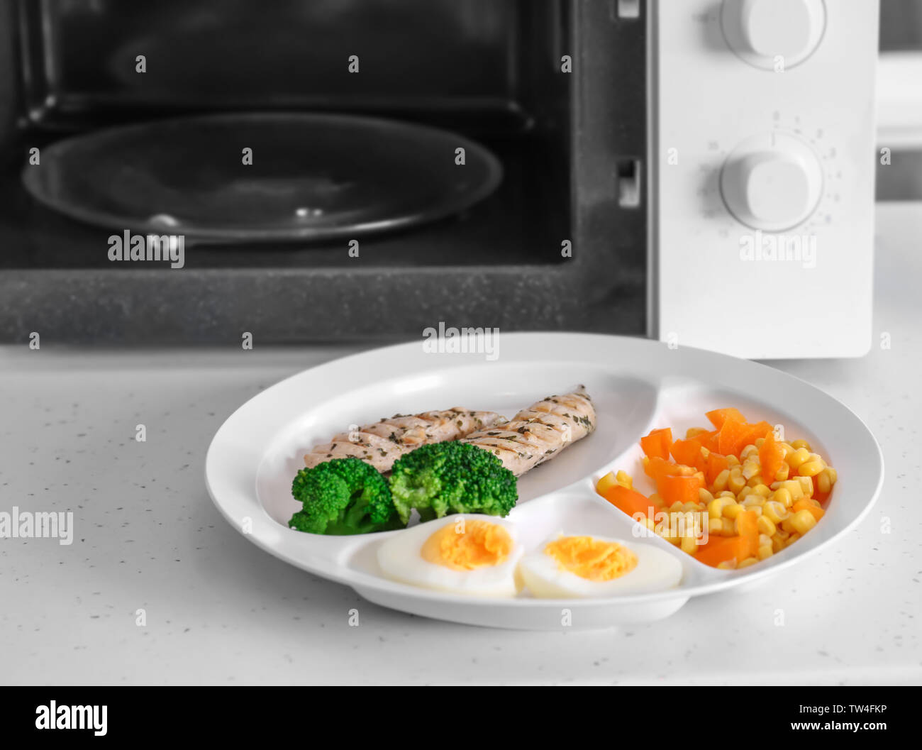 Plate with tasty organic food near microwave on table - Stock Image
