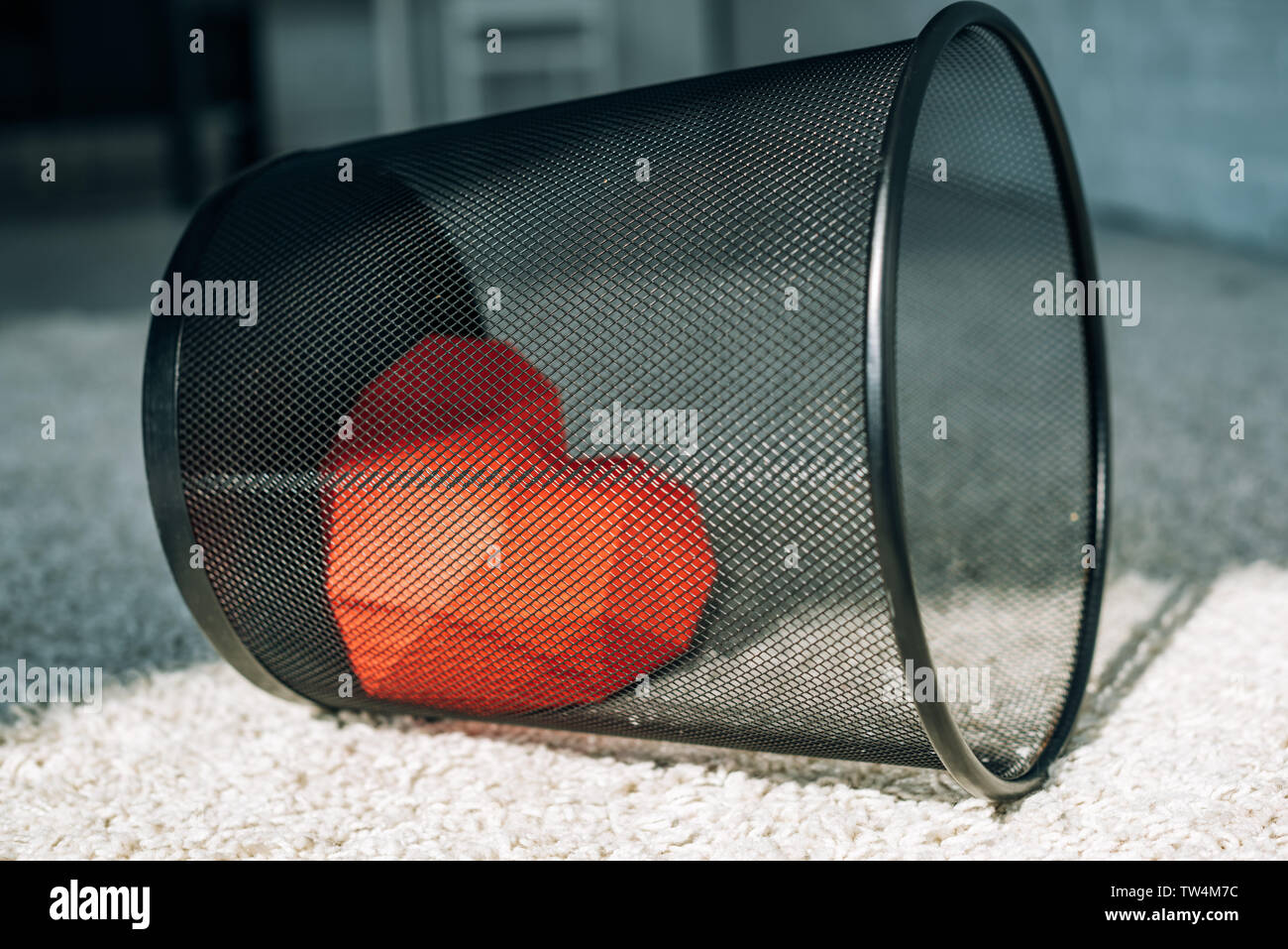 red heart in black trash can on carpet - Stock Image