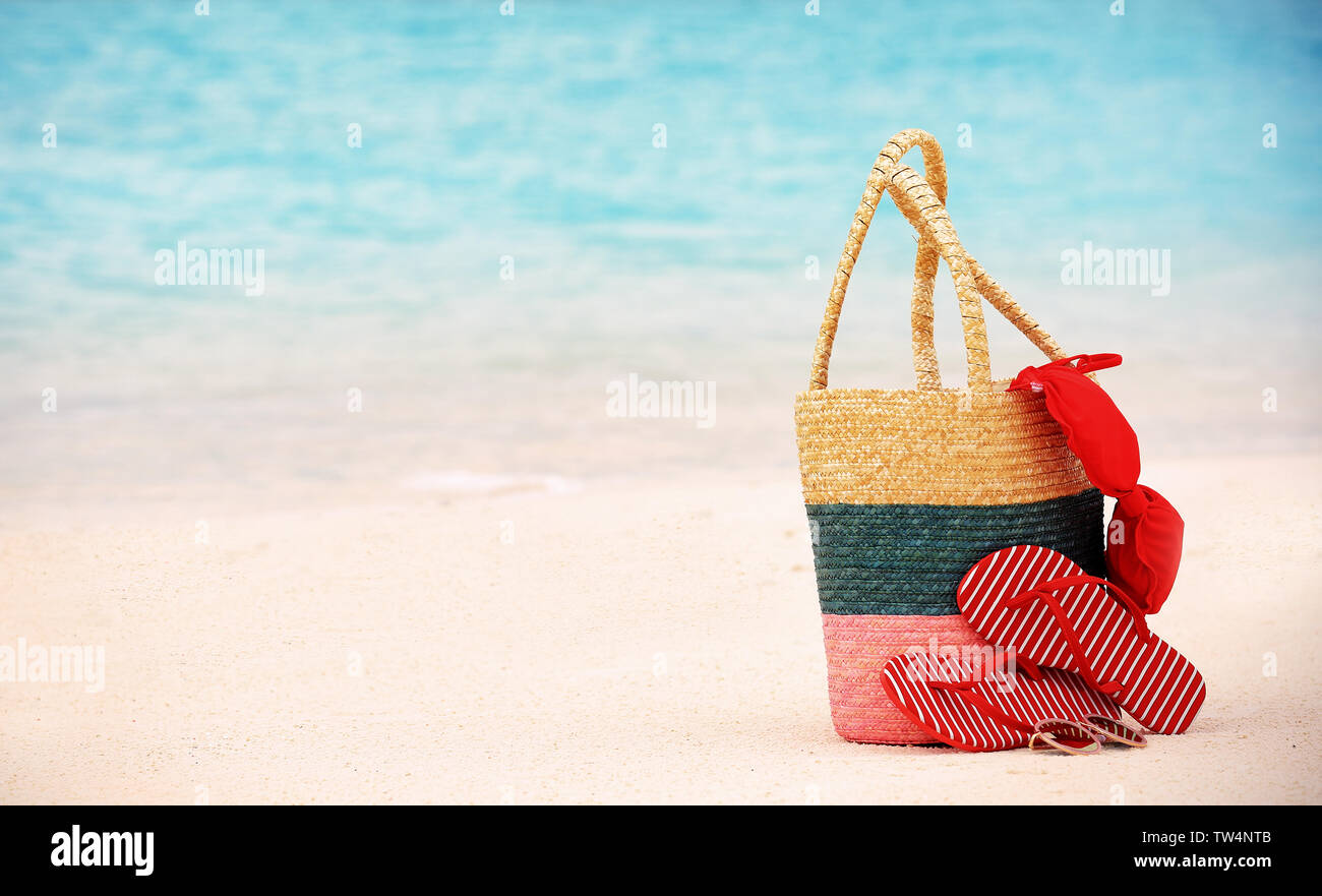 Bag with flip-flops and swimming suit on sea beach. Summer vacation concept - Stock Image