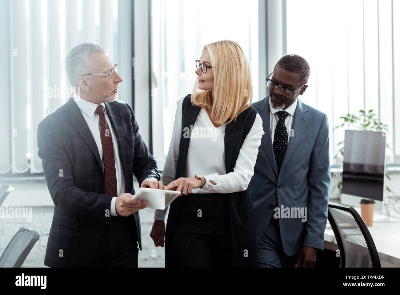 blonde businesswoman looking at coworker while pointing with finger at digital tablet near african american man Stock Photo