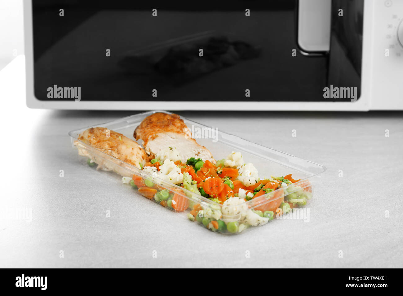 Plastic food container with delicious fried meat and baked vegetables on table - Stock Image