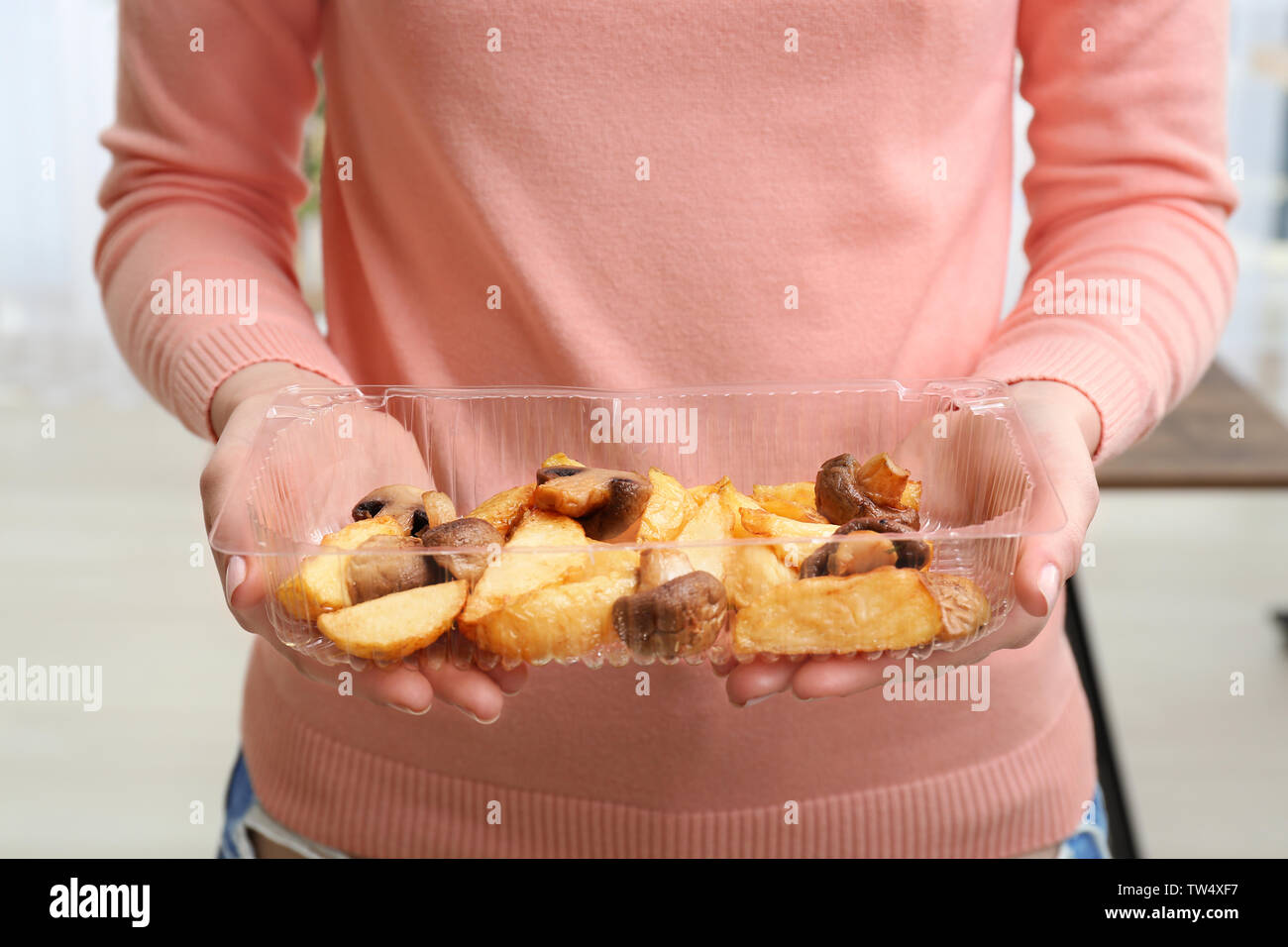 Woman holding plastic food container with tasty potato and mushrooms, closeup - Stock Image