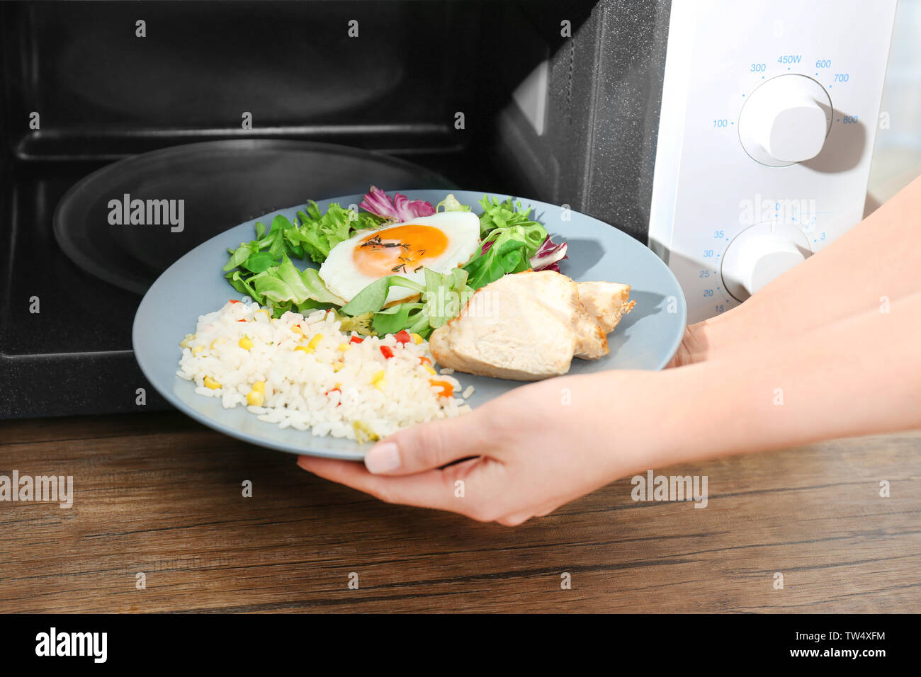 Woman putting plate with nutritious food into microwave in kitchen - Stock Image