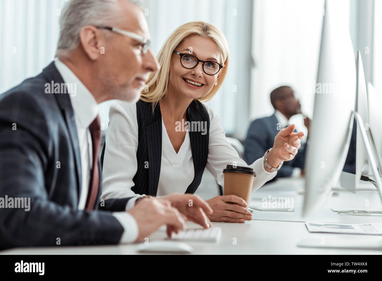 selective focus of blonde smiling businesswoman in glasses pointing with finger while looking at coworker Stock Photo
