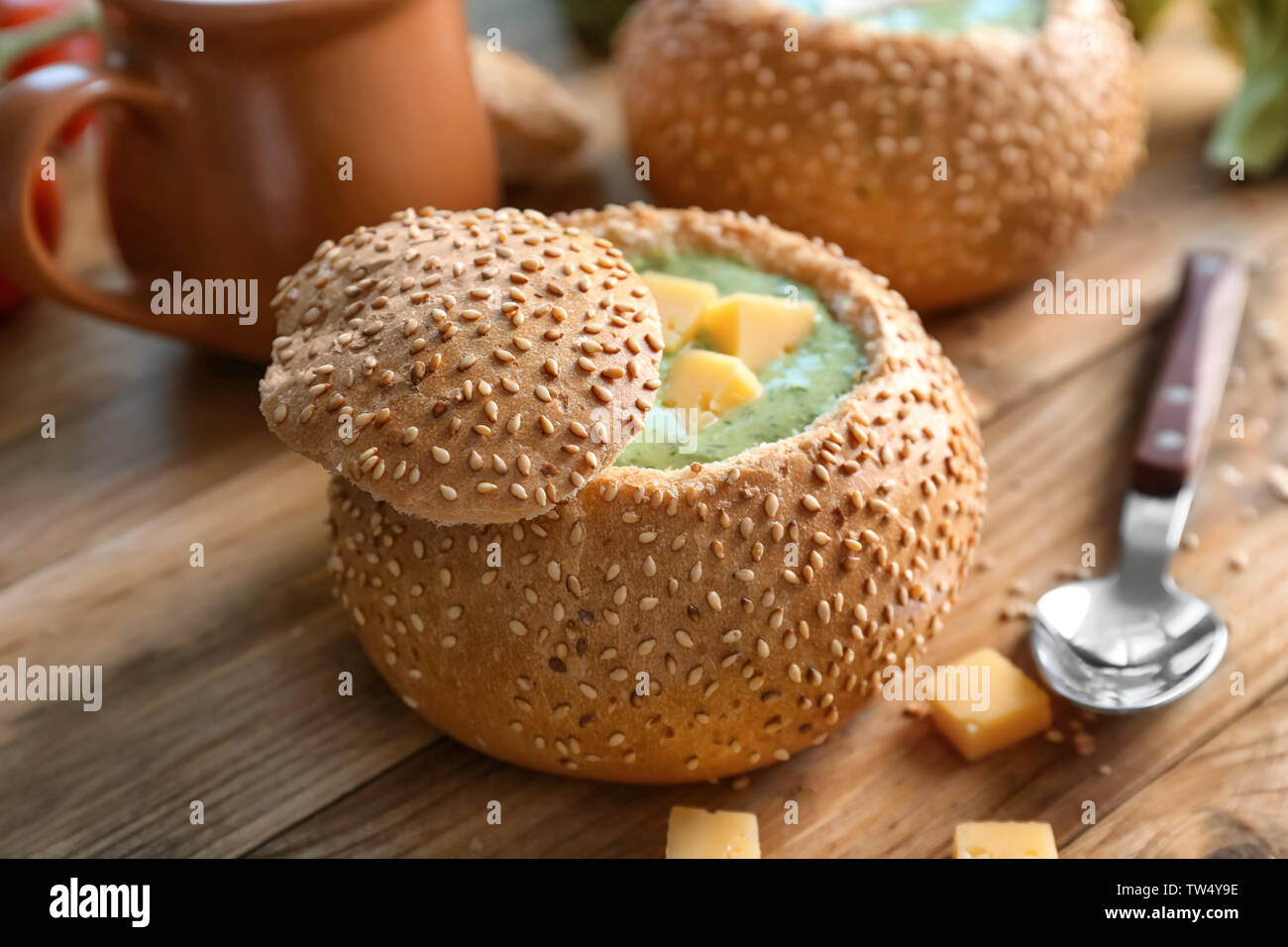 Broccoli cheese soup in bread bun on wooden table - Stock Image