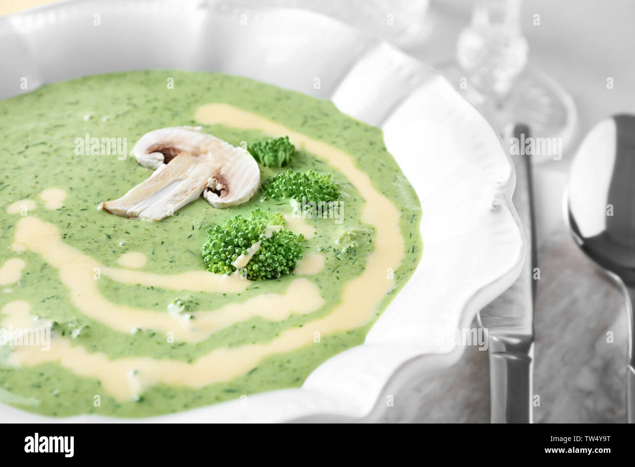 Plate with delicious broccoli cheese soup on table, closeup - Stock Image
