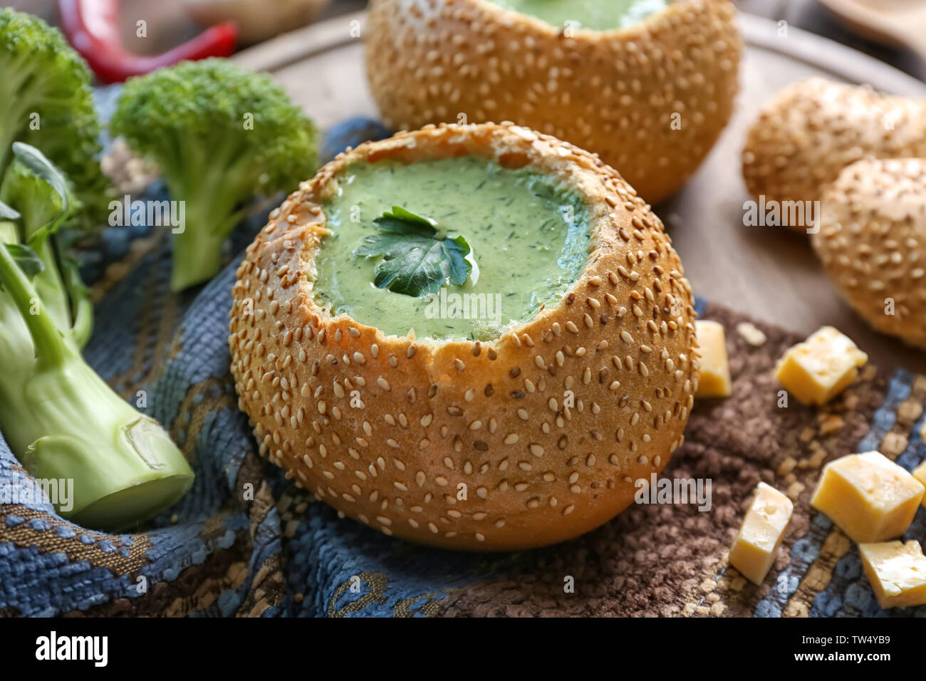 Broccoli cheese soup in bread bun on wooden board - Stock Image