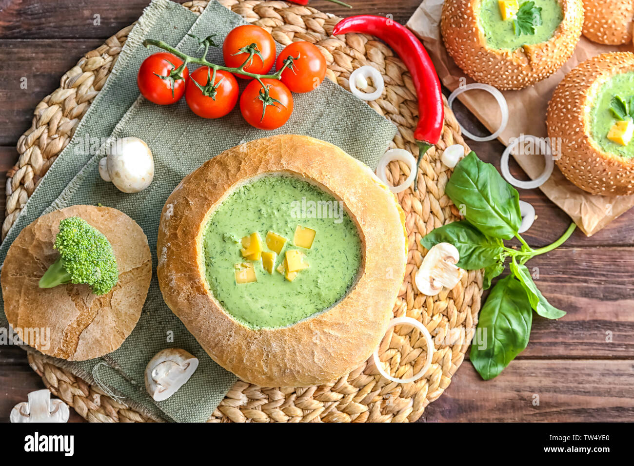 Broccoli soup with cheese in bread loaf on table - Stock Image