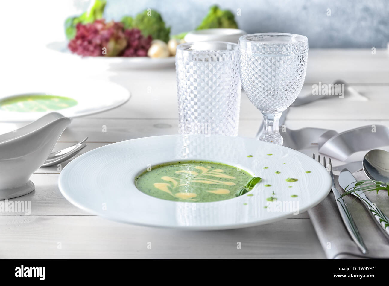 Plate with delicious broccoli cheese soup on table - Stock Image