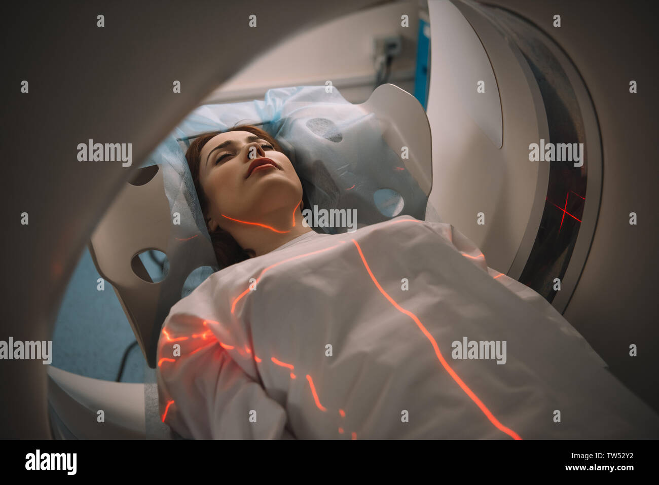 beautiful woman lying on ct scanner bed during tomography test in hospital Stock Photo