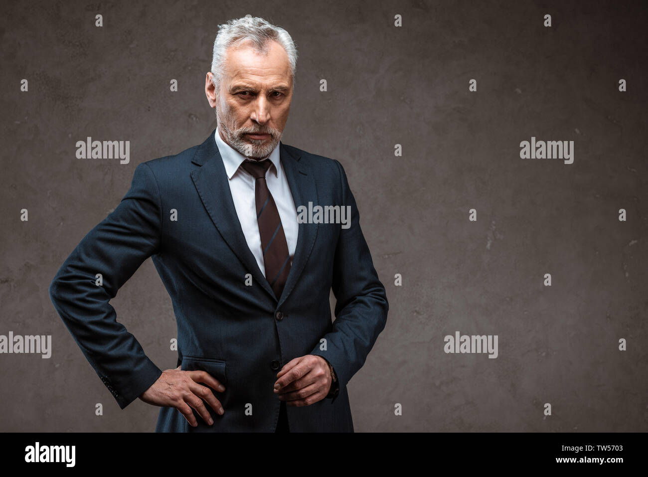 confident businessman in suit standing with hand on hip on grey - Stock Photo
