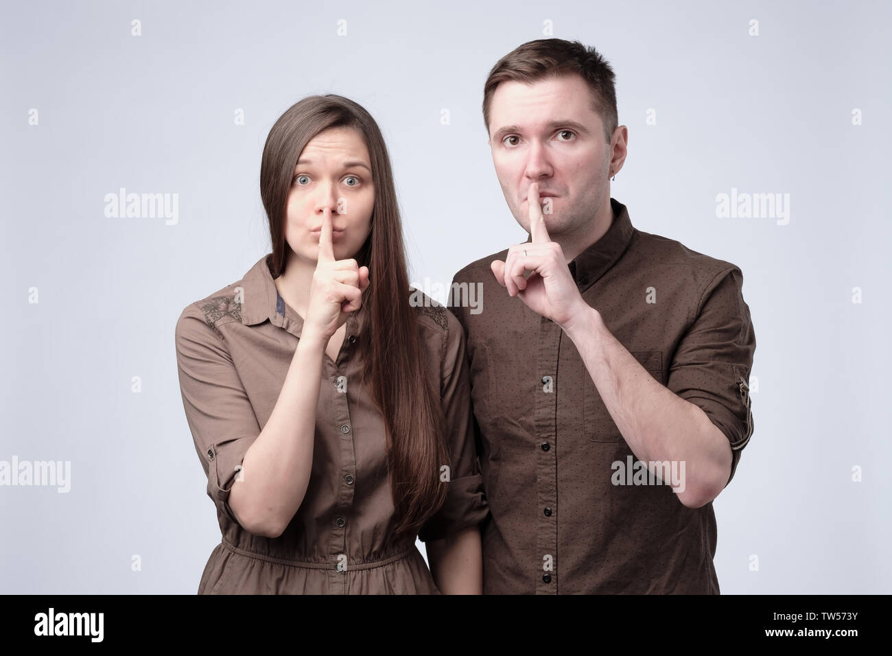 Young man and woman holding their fingers on lips asking to be silent - Stock Image