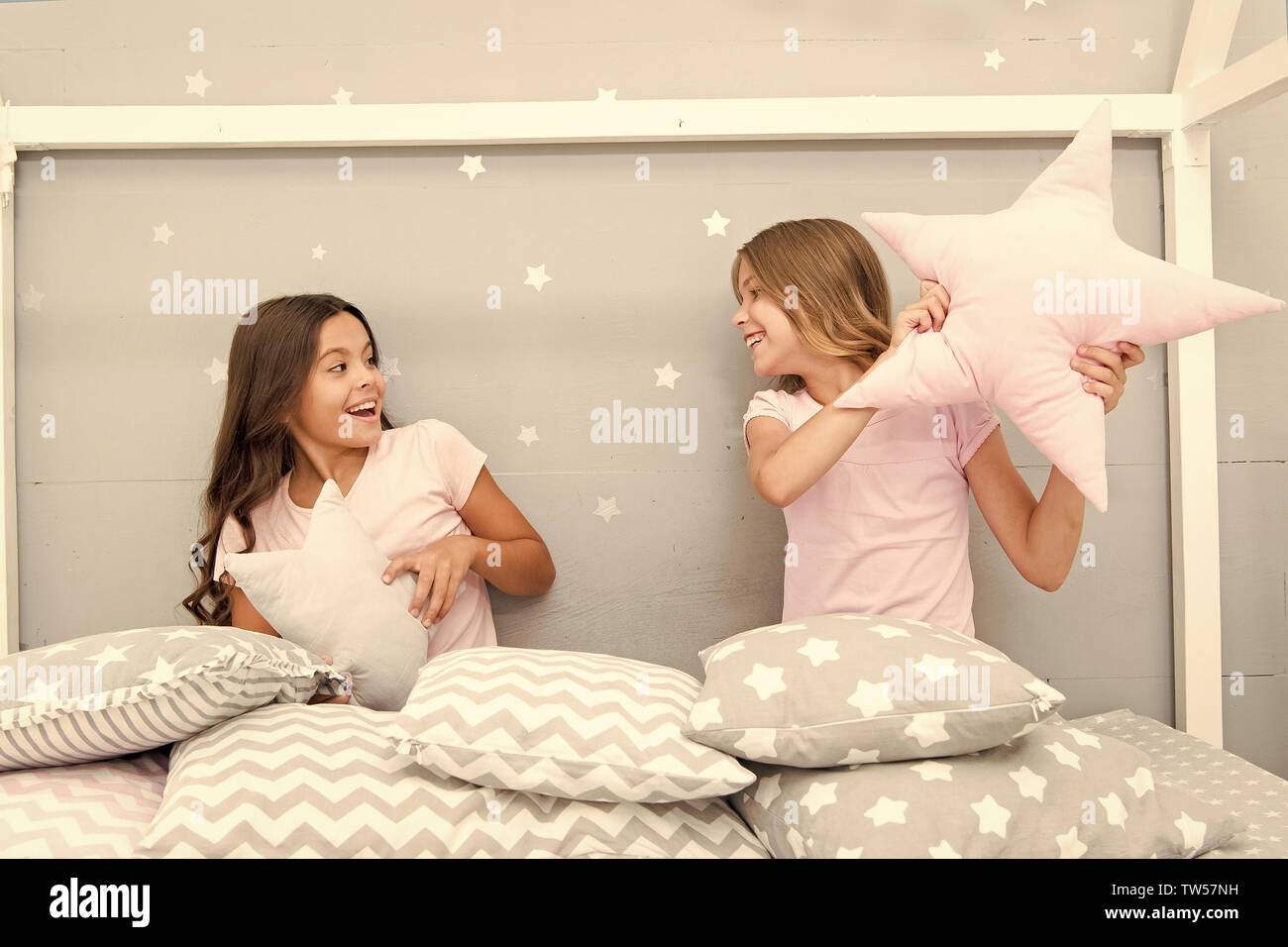 Girls sleepover party ideas. Soulmates girls having fun sleepover party. Girls happy best friends in pajamas with pillows sleepover party. Pillow figh - Stock Image