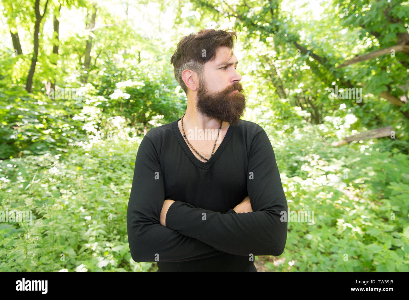 Wild nature. Man bearded hipster bright foliage background. Guy relax in forest. Exploring nature. Handsome man with beard and mustache in nature. Brutality of jungles concept. Summer heat season. - Stock Image
