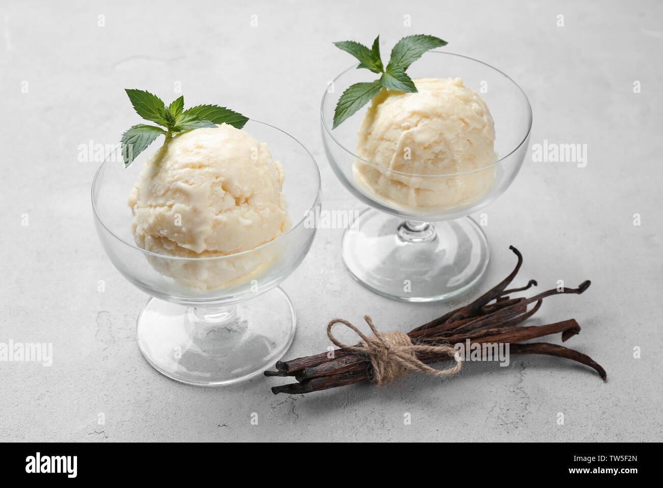 Delicious vanilla ice cream in glass dessert bowls on light background Stock Photo