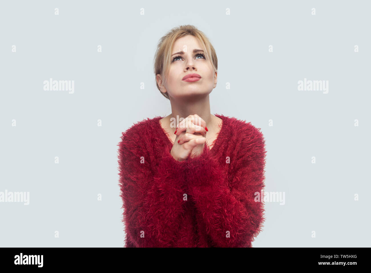 Oh my God please help me. Portrait of worry sad beautiful young blond woman in red blouse standing with palm hands, pray and looking at up. indoor stu - Stock Image