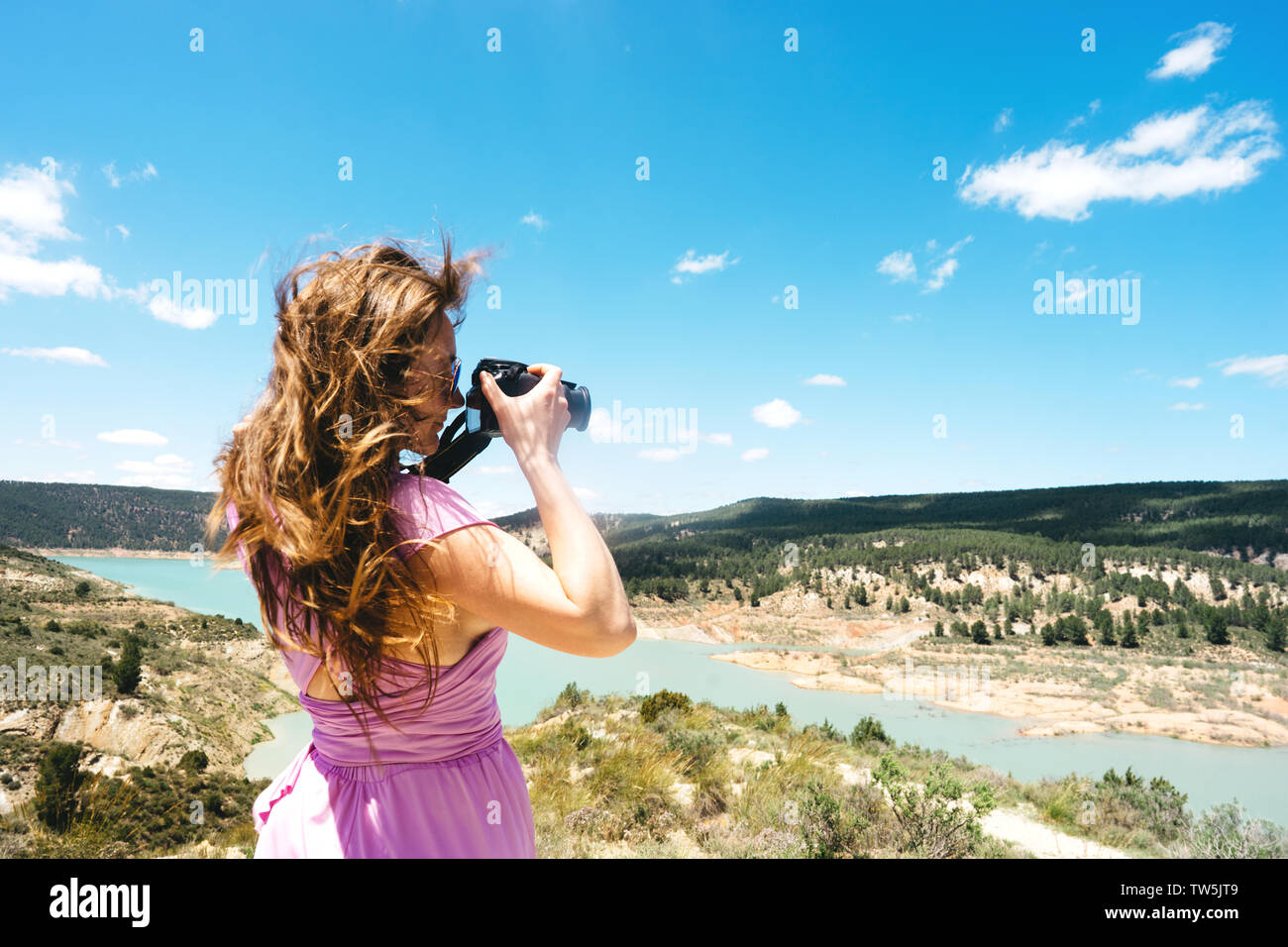 Long-haired female tourist in a pink dress with a camera stands in the mountains - Stock Image