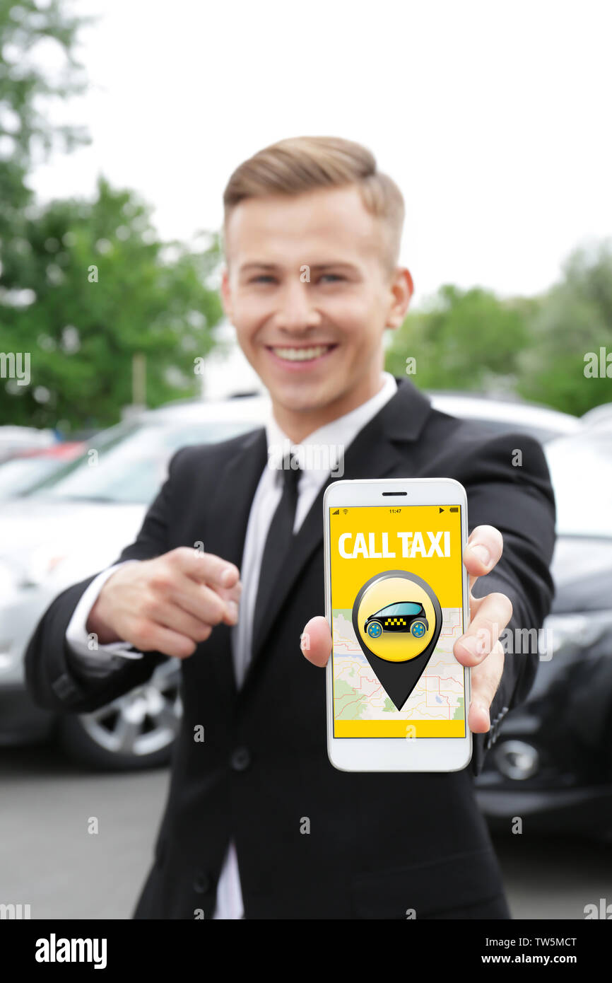 Young man calling taxi by cellphone outdoors - Stock Image