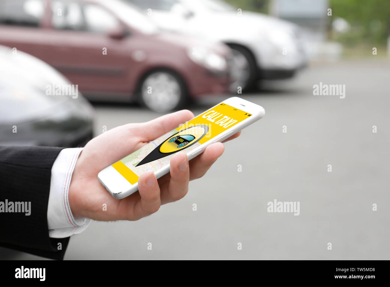 Young man using application on phone for calling taxi outdoors - Stock Image
