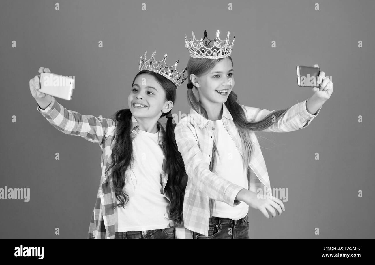 Girls taking selfie photo smartphone camera. Spoiled children concept. Egocentric princess. Kids wear golden crowns symbol princess. Warning signs of - Stock Image