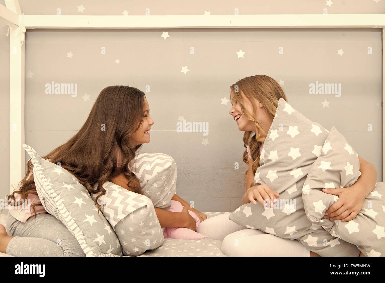 Sleepover time for pillow fight. Girls sleepover party ideas. Soulmates girls having fun sleepover party. Girls happy best friends in pajamas with pil - Stock Image