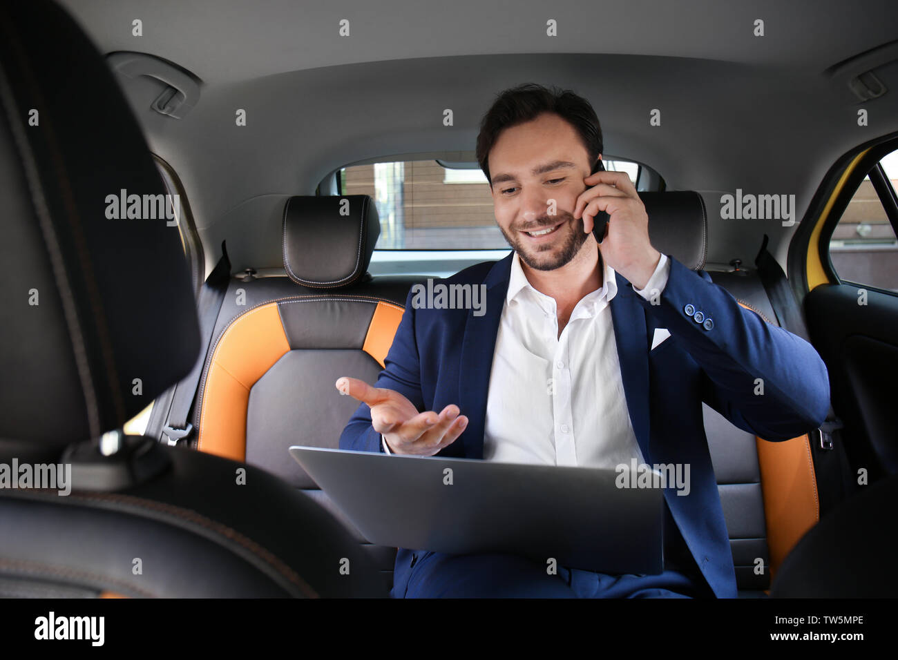 Handsome man with laptop talking on phone while sitting in taxi car - Stock Image