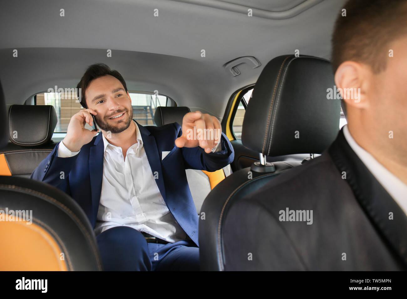 Handsome man talking on phone while sitting in taxi car - Stock Image