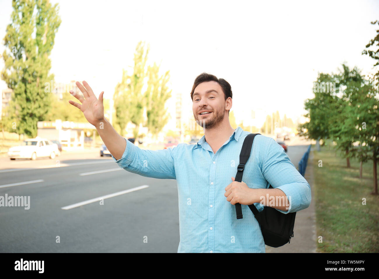 Young man catching taxi on street - Stock Image