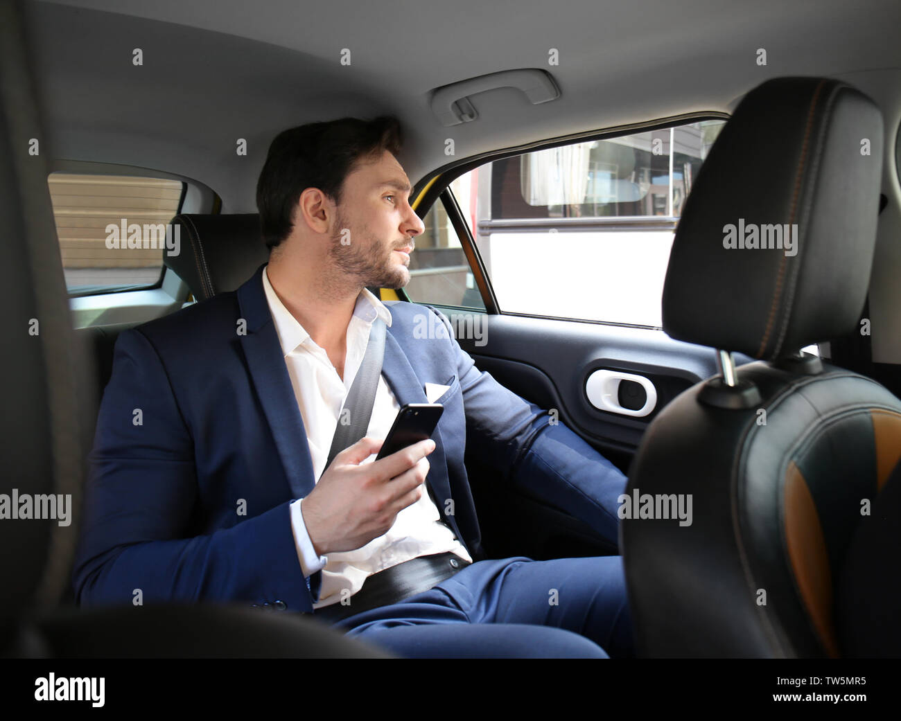 Handsome man with phone sitting in taxi car - Stock Image