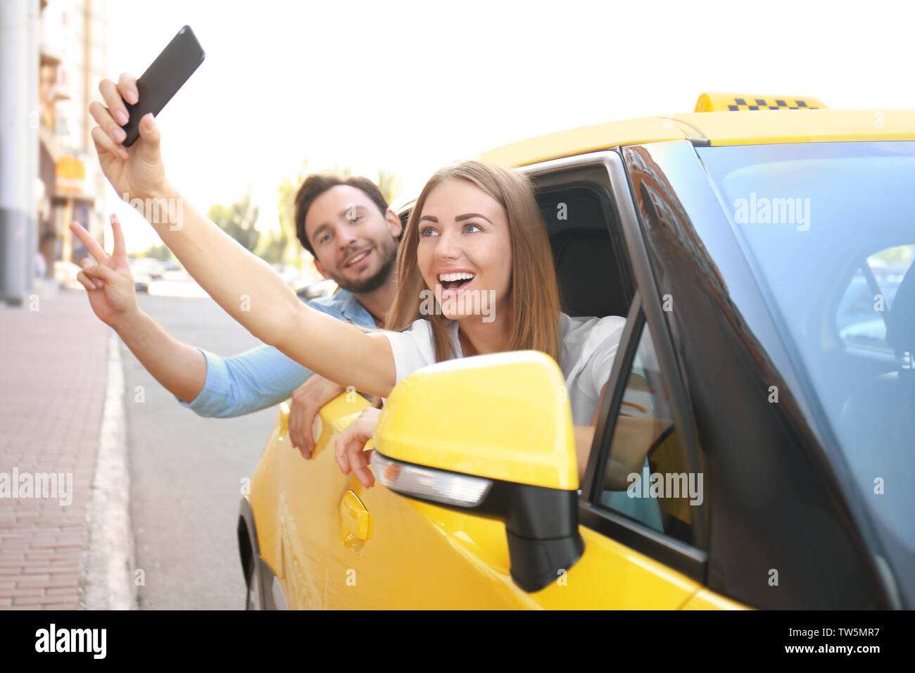 Young couple taking selfie while sitting in taxi car - Stock Image