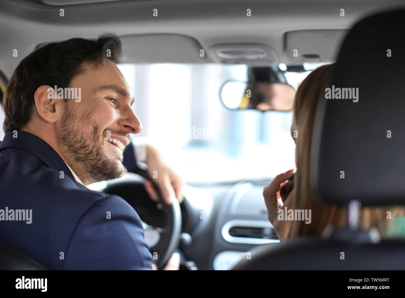Handsome driver and beautiful female passenger in car - Stock Image