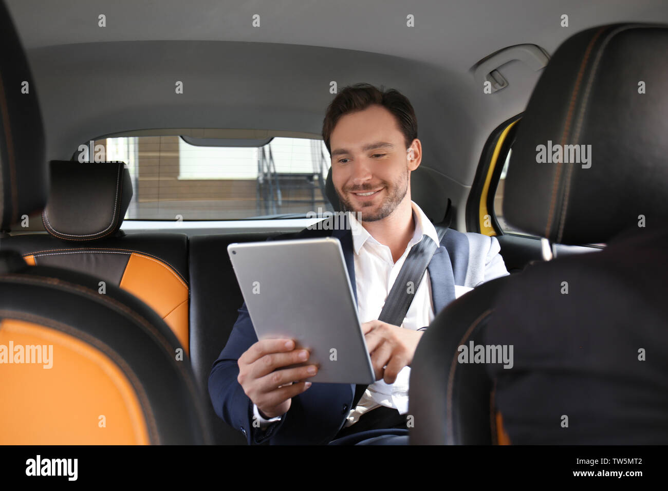 Handsome man with tablet sitting in taxi car - Stock Image