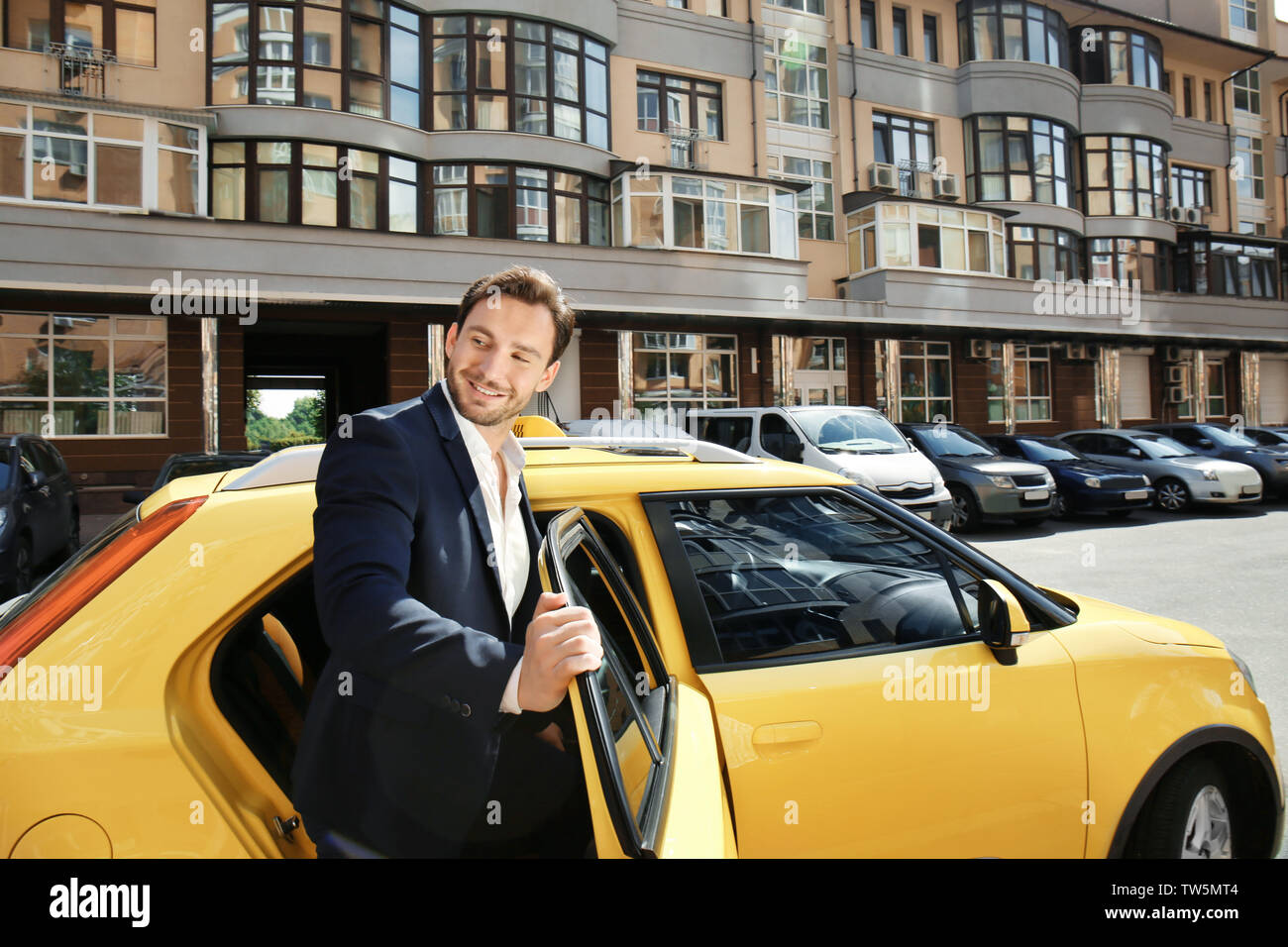 Young man standing near taxi car on street - Stock Image