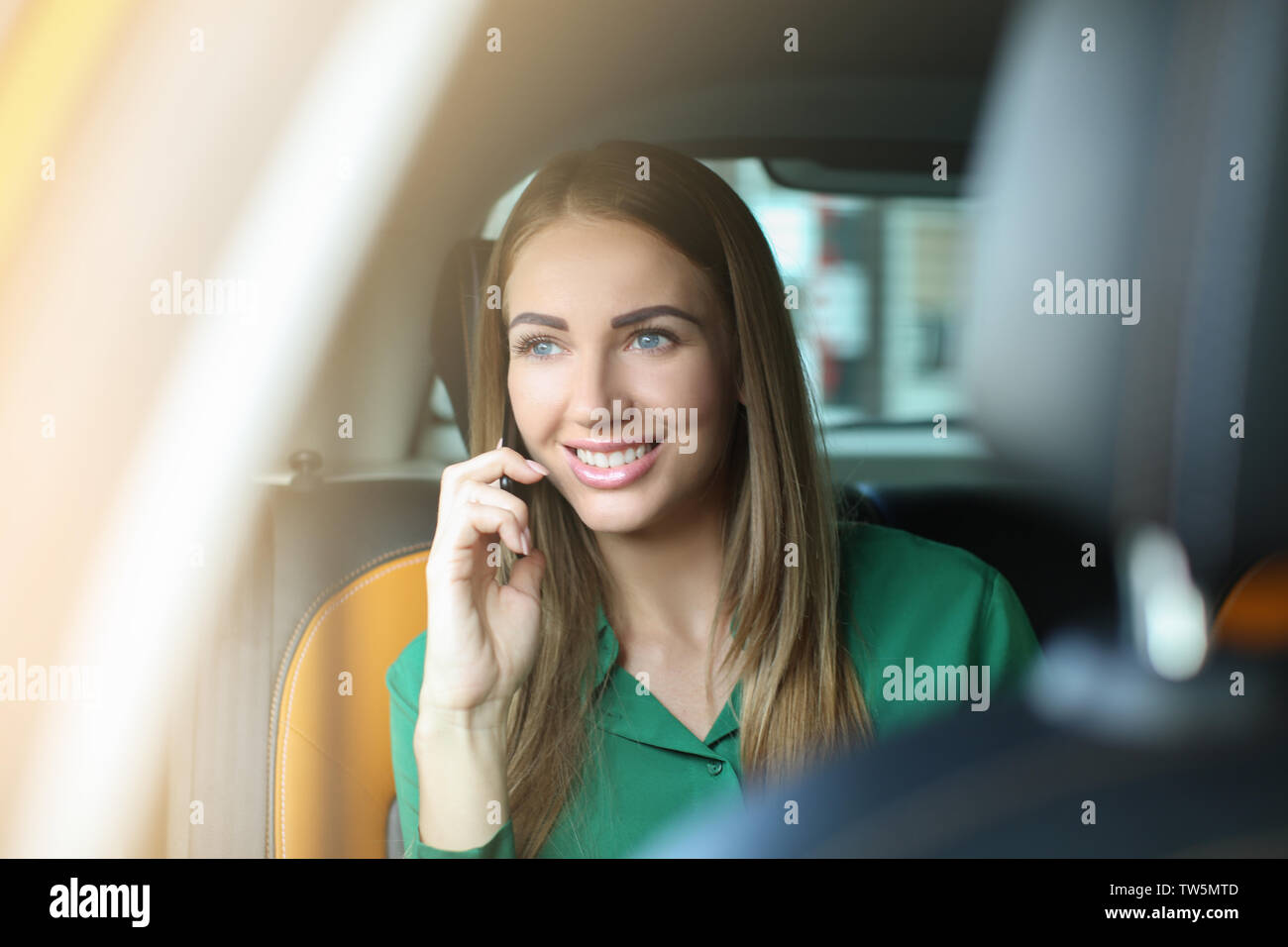 Beautiful woman talking on phone while sitting in taxi - Stock Image